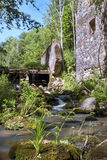 Old, abandoned water mill with water streams and little waterfalls. Old and abandoned water mill on the river Pakrace in Latvia Stock Image