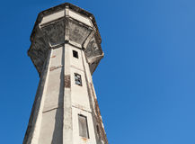 Old abandoned water tower above blue sky Stock Photos