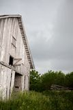 Old, Abandoned, Weathered Barn Door Swings in Stor. An old, abandoned, gray, weathered barn faces another storm while the wind tries to swing a hay loft door off Royalty Free Stock Photos