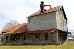 Old abandoned wood barn with porches and roof in disrepair. Old, abandoned wood barn, with windows boarded over and porches and roof in disrepair Stock Image