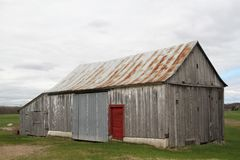 Old abandoned wood  barn with red door Stock Image