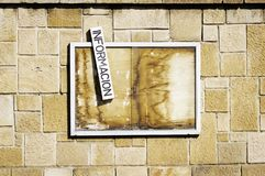 An old abandoned wooden billboard hanging on a wall. With a sign with the Spanish word for information stock images