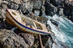 Old abandoned wooden boat crashed on rocks of Santorini island Royalty Free Stock Image