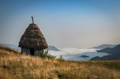 Old abandoned wooden cabin on top above a valley in fog. Old abandoned wooden cabin on top above a valley covered in fog stock images