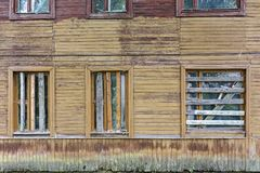 Old abandoned wooden house facade. Old abandoned and destroyed wooden house facade. boarded up windows on wall stock image