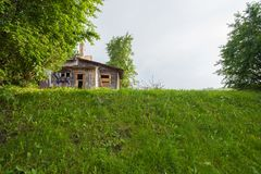 Old abandoned wooden house with a flowing wooden roof. Green vegetation and hills around royalty free stock images