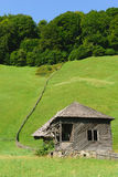 Old abandoned wooden house with green grass hills in the background Royalty Free Stock Photos
