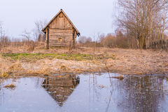 Old abandoned wooden house, a hut in the village with one small window is located near the pond, the house and the blue sky are re Stock Image