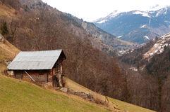 Old abandoned wooden house on a mountain. Old abandoned wooden house with a roof of corrugated sheet standing high on a mountain Royalty Free Stock Photography