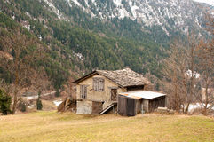 Old abandoned wooden house on a mountain. Old abandoned wooden house with windows boarded up with weathered wood and a roof of slate tiles Royalty Free Stock Images