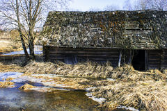 Old abandoned wooden house by the river in spring stock image