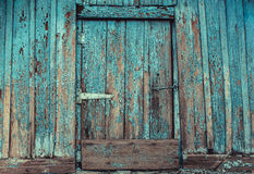 Old, abandoned, wooden, painted in blue, cracked, rotten door with a hook from the hut. Royalty Free Stock Photography