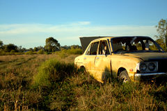 An Old Abandoned Yellow Car. An old abandoned smashed up yellow car or sedan in a field of grass and weeds Royalty Free Stock Photos