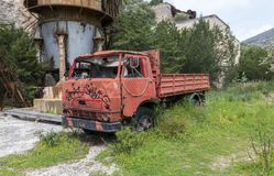 Old abandonned red car in old mine on sardinia island. Golfo Aranci,Italy,08-April-2018:old abandonned urban metal mine with rusty red car left by the workers royalty free stock photos