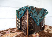 An old accordion covered with a rug. The property of times royalty free stock photography
