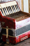 Old accordion. Located on the old accordion red wood tables royalty free stock photos