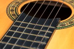 Old acoustic guitar. Closeup wooden classical guitar. Old classical guitar with nylon strings. Old acoustic guitar royalty free stock image