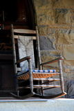 Old Adirondack rocking chair against stone wall Stock Image