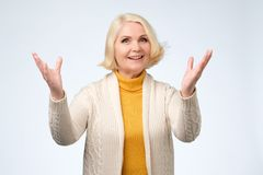 Old adult blonde excited cheerful astonished lady smiling, laughing. Raising hands up over grey background. Positive facial emotion stock photos