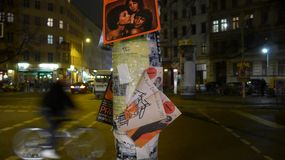 An old advertising pillar with ripped off posters. At a crossroads.At night in the streets of Berlin, Germany, Europe Royalty Free Stock Photos