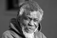 Old African American homeless man. Portrait of old African American homeless man in black in white outdoors Stock Photography