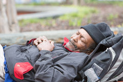 Old african american homeless man sleeping. Outside during the day Stock Photography