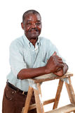 Old african man leaning on a ladder. Old african man on a wooden ladder with folded hands stock photo