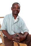 Old african man sitting on ladder. Old african man sitting on a wooden ladder with folded hands stock photo