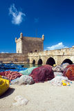 Old african port. Colored fishnets and boats with stone rampart and tower in old port in Essaouira, Morocco, Africa Stock Images
