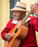 Old afrocuban street musician playing the guitar in Havana. Old afrocuban street musician playing the guitar next to a colonial house.2 850 000 foreign tourists Royalty Free Stock Photo
