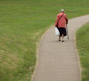 Old age. Elderly female with walking stick on deserted, winding path. Plenty of space to add text Stock Photos