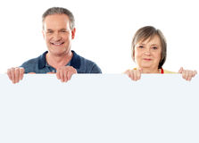Old age couple holding blank banner ad. Against white background Stock Image
