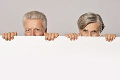 Old age couple holding blank banner Royalty Free Stock Images