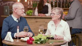 Old age couple on a romantic date in a vintage restaurant stock footage