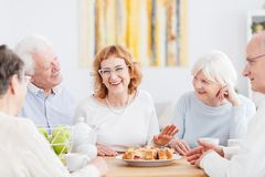 Happy seniors chatting at cafe. Old age, friendship and people concept, group of attractive happy seniors chatting and having fun together in a cafe Stock Images