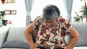 Old age, health problem and people concept - Asian senior woman suffering from pain in back or reins at home.  stock footage