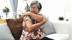Old age, health problem and people concept - Asian senior woman suffering from pain in back or reins at home.  stock video footage