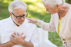 Close up of senior man with heartache at park. Old age, health problem and people concept - close up of senior men feeling heartache at summer park Stock Image