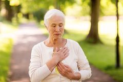 Senior woman feeling sick at summer park. Old age, health problem and people concept - senior woman feeling sick at summer park Stock Image