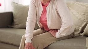 Senior woman suffering from pain in leg at home stock video