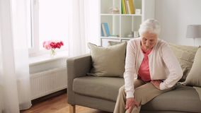 Senior woman suffering from pain in leg at home stock video footage