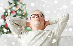 Senior man in glasses relaxing on sofa Royalty Free Stock Images