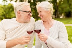 Happy senior couple drinking wine at summer park. Old age, holidays, leisure and people concept - happy senior couple clinking wine glasses at summer park Stock Images