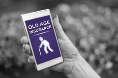 Old age insurance concept on a smartphone. Female hand holding a smartphone with old age insurance concept royalty free stock image