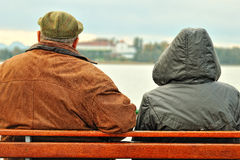 Old age people on the bench. Two old age people staying on the bench of the boate and looking at the Herrenchiemsee island on the Chiemsee lake in Bavaria royalty free stock image