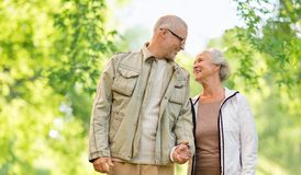 Happy senior couple over green natural background. Old age and people concept - happy senior couple holding hands over green natural background royalty free stock photography