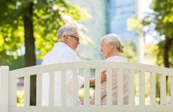 Happy senior couple sitting on bench at park. Old age, relationship and people concept - happy senior couple sitting on bench at summer park Stock Images