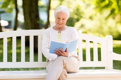Happy senior woman reading book at summer park. Old age, retirement and people concept - happy senior woman reading book sitting on bench at summer park Royalty Free Stock Photography