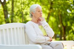 Sad senior woman sitting on bench at summer park. Old age, retirement and people concept - sad senior woman in glasses sitting on bench at summer park Royalty Free Stock Photo
