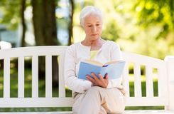 Senior woman reading book at summer park. Old age, retirement and people concept - senior woman reading book sitting on bench at summer park Royalty Free Stock Photography
